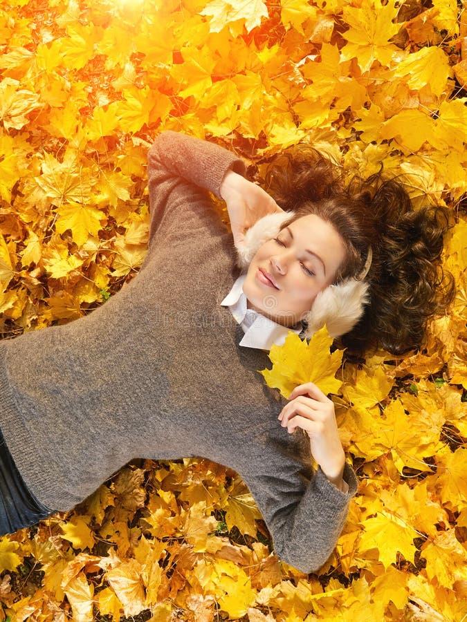 Menina bonita nova que aprecia o dia que encontra-se nas folhas amarelas, vista do outono de cima de fotografia de stock royalty free