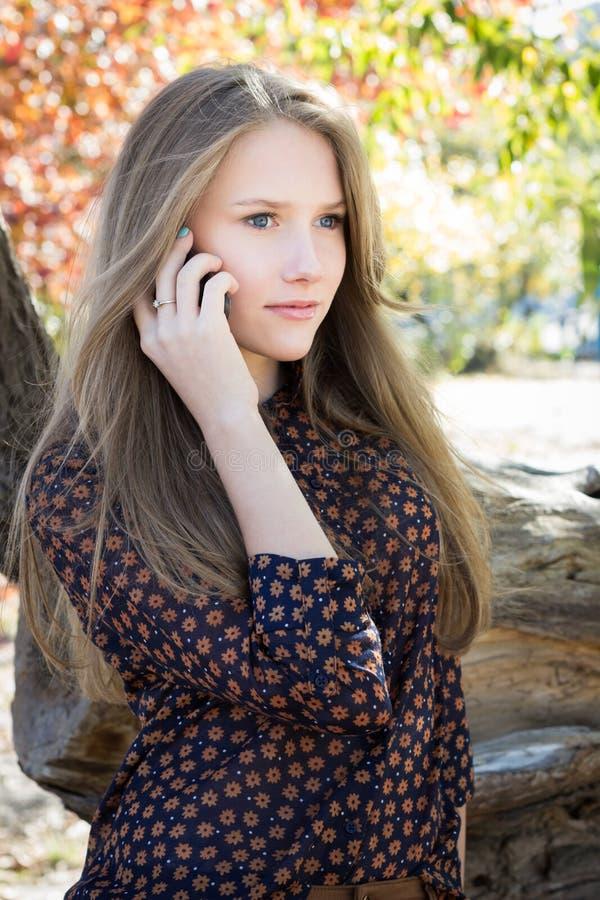 Menina bonita nova que chama o telefone celular no parque fotografia de stock royalty free