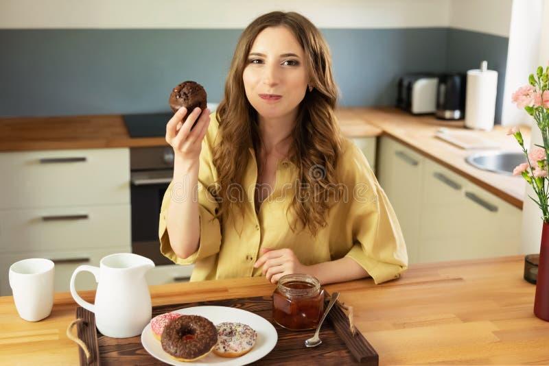 Menina bonita nova que come o café da manhã em casa na cozinha imagem de stock