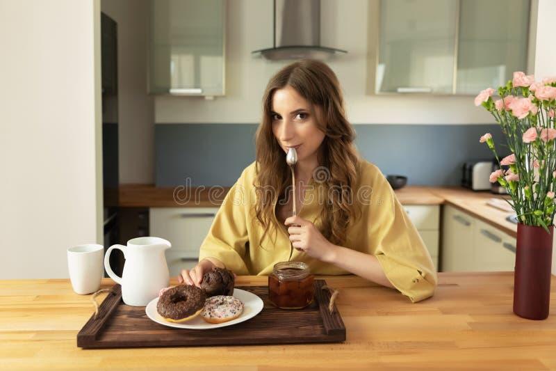 Menina bonita nova que come o café da manhã em casa na cozinha fotografia de stock