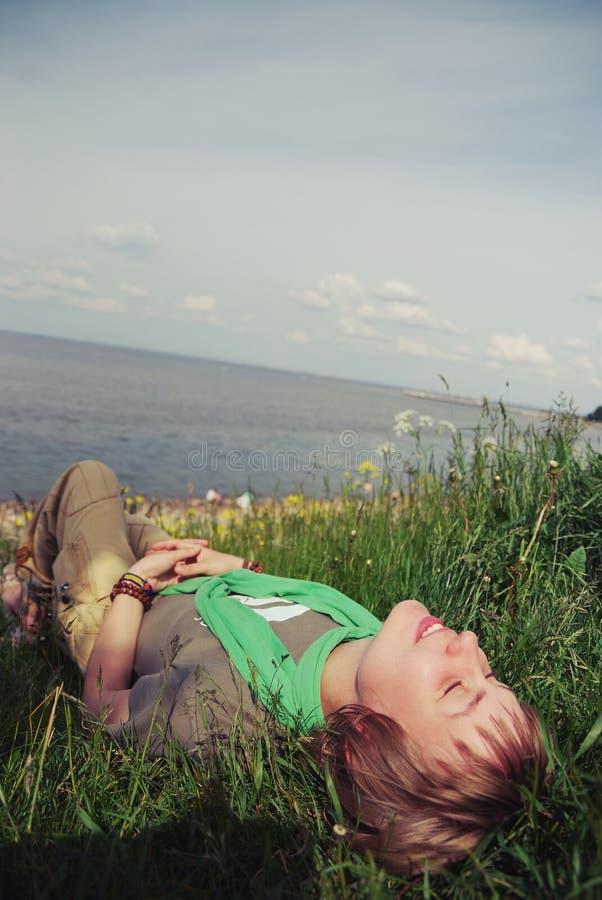 Menina bonita nova que encontra-se com seus olhos fechados e um sorriso no seu cara a grama verde o dia ensolarado morno da baía fotos de stock