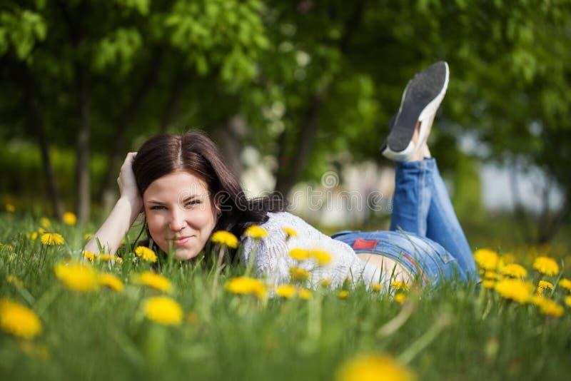 Menina bonita nova que encontra-se em uma grama Campo do verão com flor fotografia de stock