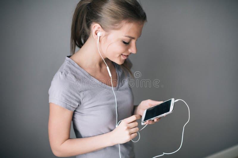 Menina bonita nova que escuta a música com fones de ouvido ao mostrar o telefone celular da tela vazia sobre o cinza imagens de stock royalty free