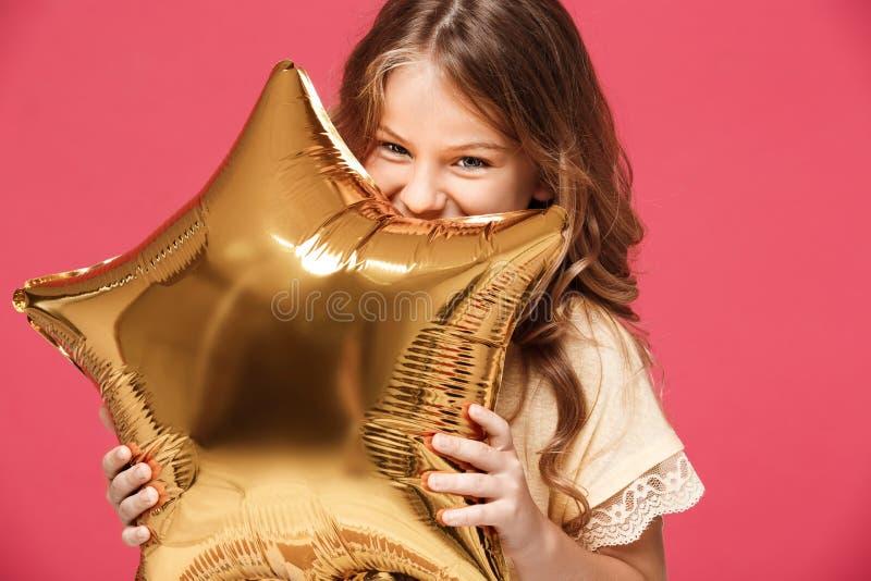 Menina bonita nova que guarda o baloon e que sorri sobre o fundo cor-de-rosa imagens de stock royalty free