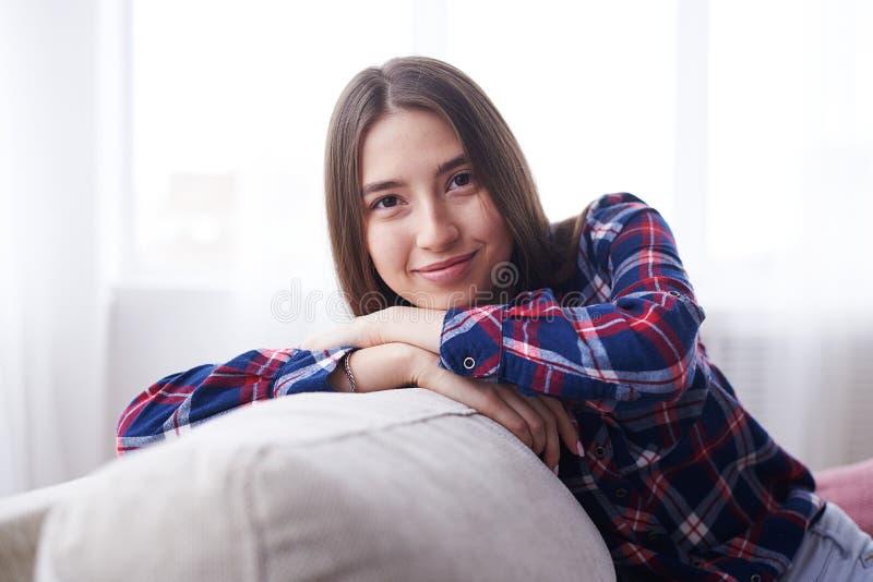 Menina bonita nova que inclina-se na parte de trás do sofá imagem de stock