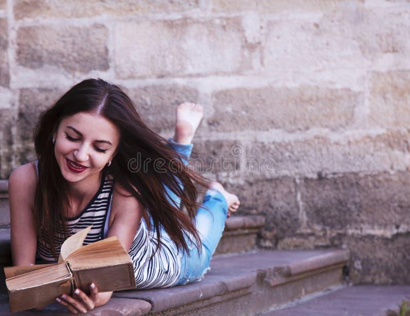 Menina bonita nova que lê uma educação do livro fora, auto de imagens de stock royalty free