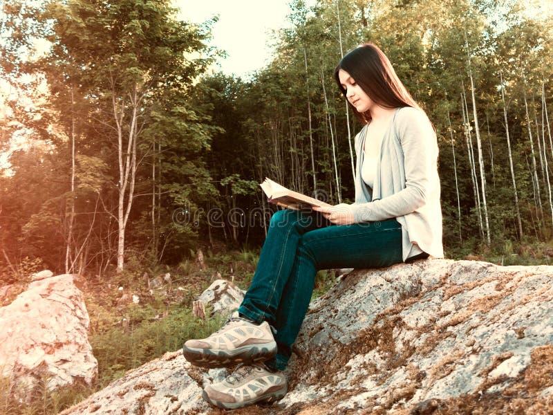 Menina bonita nova que l? um livro que senta-se em uma grande rocha na floresta imagens de stock royalty free