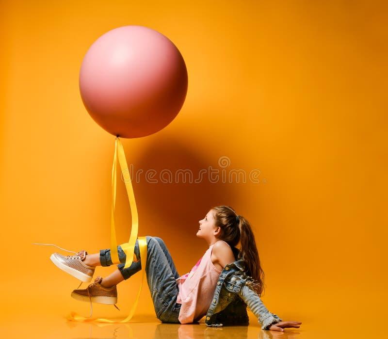 Menina bonita nova que levanta em um fundo amarelo, mentiras do adolescente e para sustentar um bal?o cor-de-rosa gigante enorme  foto de stock