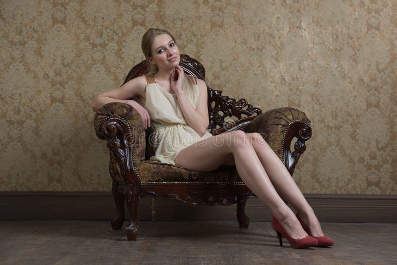 Menina bonita nova que levanta no estúdio, sentando-se na cadeira do vintage foto de stock