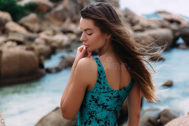 A menina bonita nova que levanta no perfil no fundo dos azuis celestes molha em um roupa de banho elegante do vidoeiro, toca deli imagem de stock