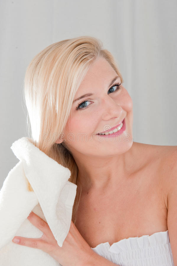 Menina bonita nova que seca o cabelo longo com uma toalha imagem de stock