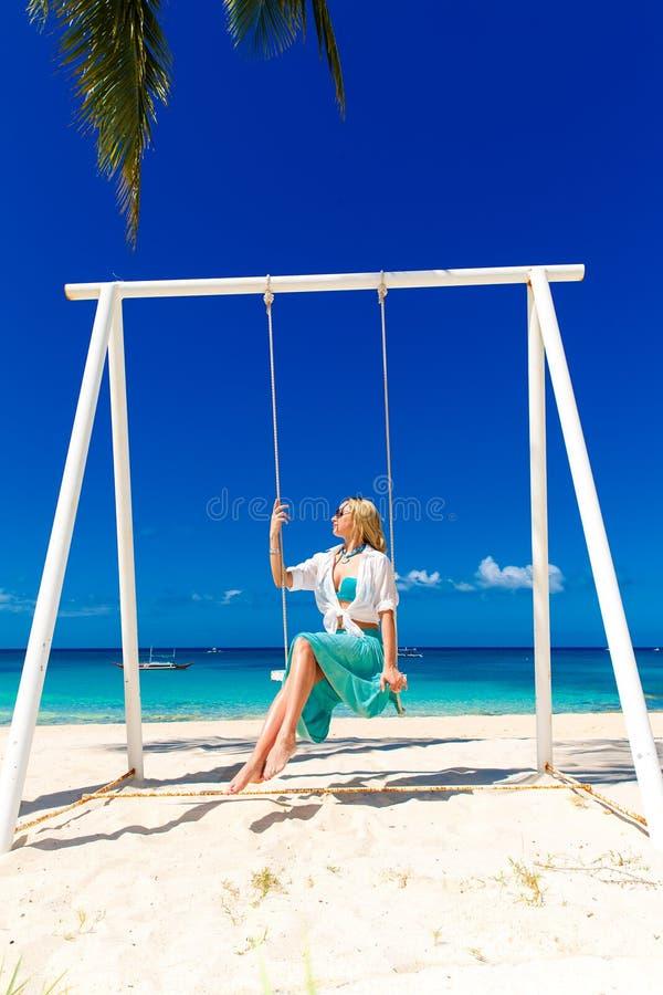 Menina bonita nova que senta-se em um balanço sob uma palmeira azul imagem de stock