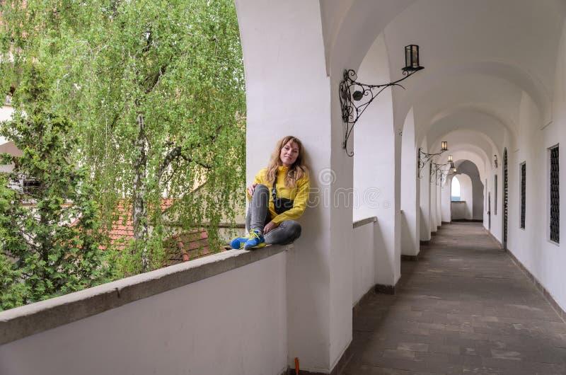 Menina bonita nova que senta-se em uma janela arqueada em um castelo antigo fotografia de stock