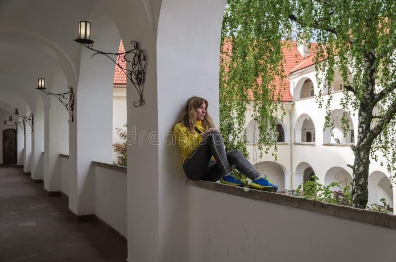 Menina bonita nova que senta-se em uma janela arqueada em um castelo antigo fotos de stock royalty free