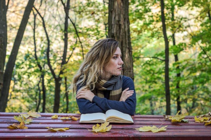 Menina bonita nova que senta-se no parque do outono atrás de uma tabela de madeira que lê um livro imagem de stock royalty free