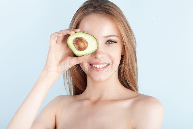 Menina bonita nova que sorri com close-up do abacate imagens de stock royalty free