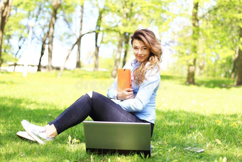 Menina bonita nova que trabalha no portátil exterior, encontrando-se na grama, caucasian 20 anos velho imagens de stock royalty free