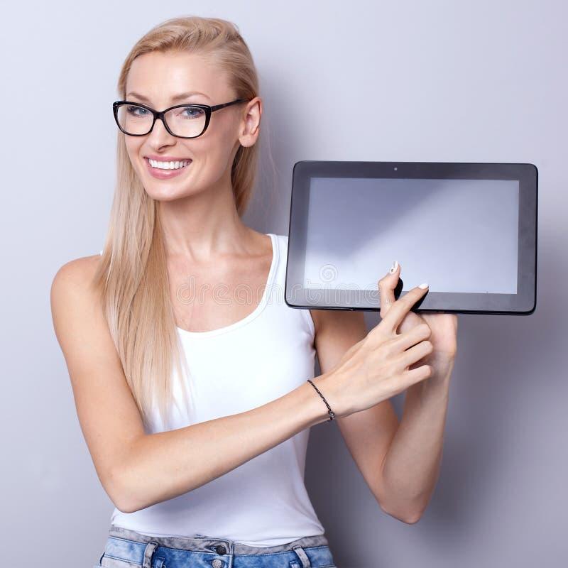 Menina bonita nova que usa a tabuleta fotografia de stock
