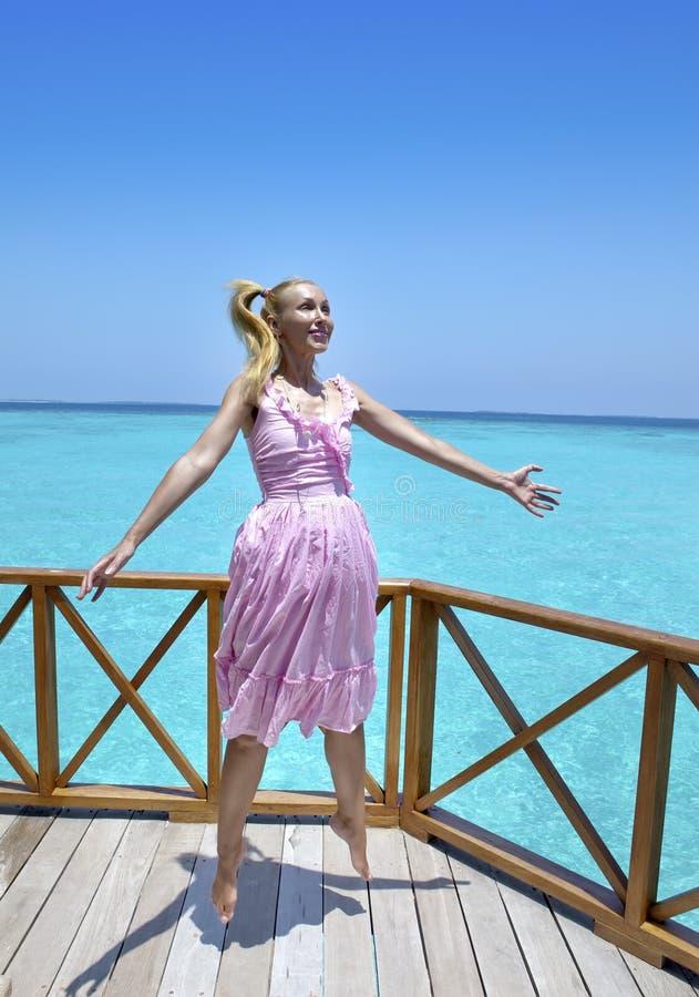 A menina bonita nova salta em sundress cor-de-rosa na plataforma da casa de campo na água sob o guarda-chuva, Maldivas fotografia de stock