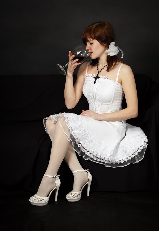 A menina bonita nova senta-se com um vidro fotos de stock royalty free