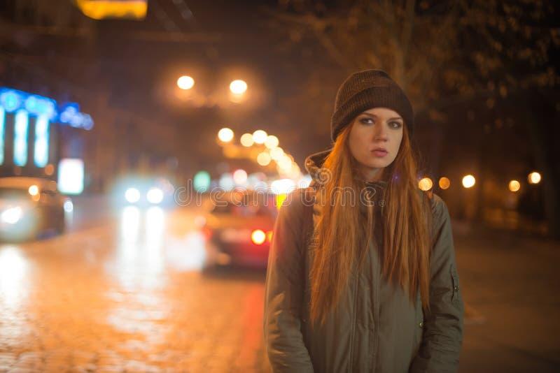 A menina bonita nova trava um táxi na rua da cidade na noite fotografia de stock royalty free