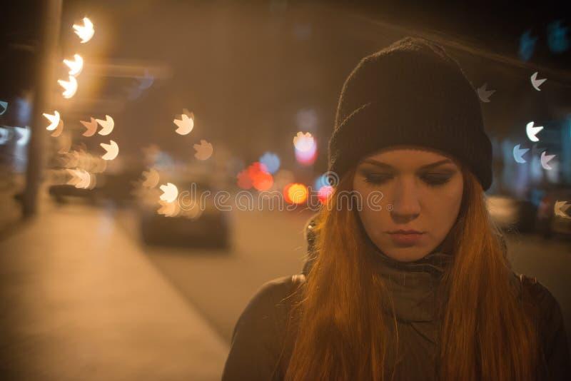 A menina bonita nova trava um táxi na rua da cidade na noite imagem de stock