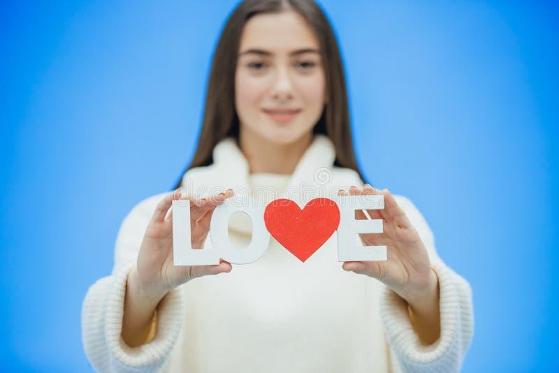 Menina bonita nova vestida na roupa branca Durante este tempo está em um fundo azul Guarda uma palavra do amor dentro imagem de stock royalty free