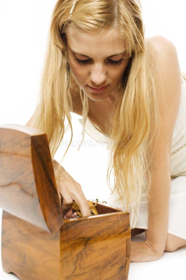 A menina bonita olha a caixa de jóia de madeira fotos de stock