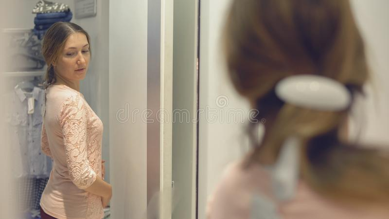 A menina bonita olha sua reflexão no espelho ao tentar na roupa na loja da forma ao comprar fotografia de stock royalty free