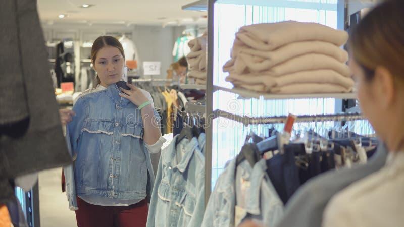 A menina bonita olha sua reflexão no espelho ao tentar na roupa na loja da forma ao comprar foto de stock