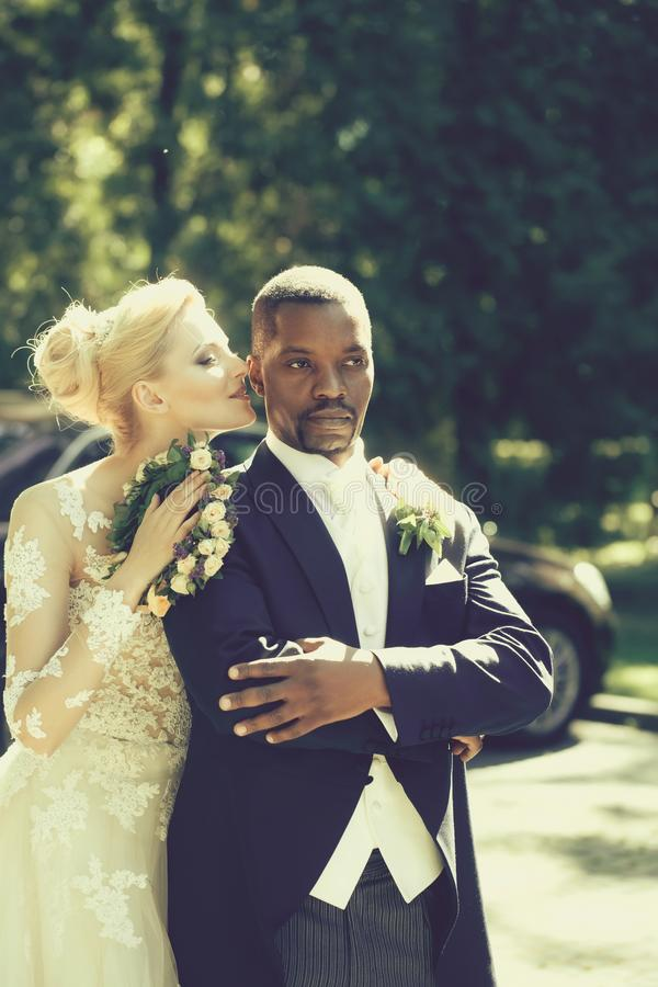 Menina bonita ou noiva bonito que abraçam o noivo afro-americano considerável fotos de stock