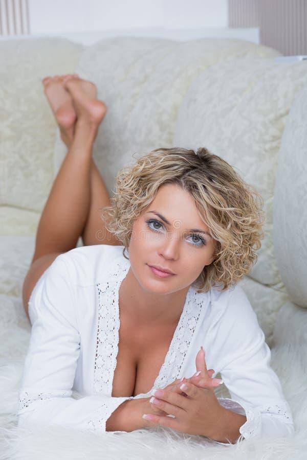 Menina bonita pechugóa que encontra-se no sofá fotos de stock royalty free