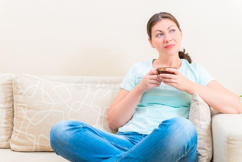 Menina bonita pensativa com um copo imagem de stock royalty free