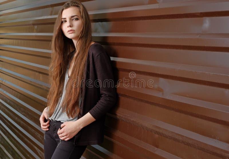 Menina bonita pensativa que olha a câmera que inclina-se para trás contra a cerca do metal com faixas paralelas Menina nova do mo imagem de stock