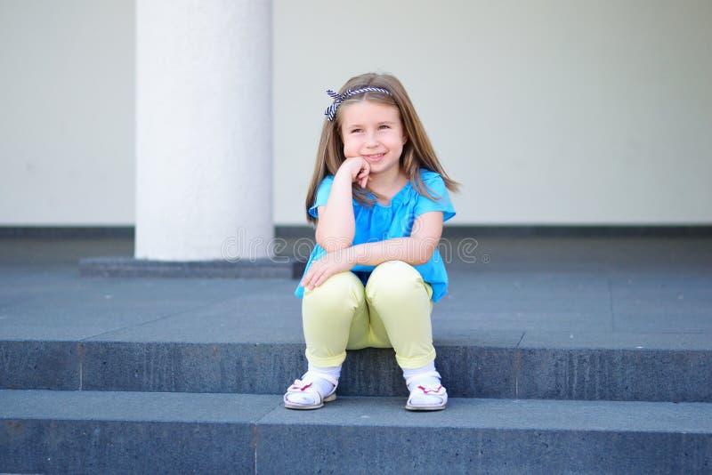 Menina bonita pequena adorável que senta-se em uma escadaria imagens de stock royalty free