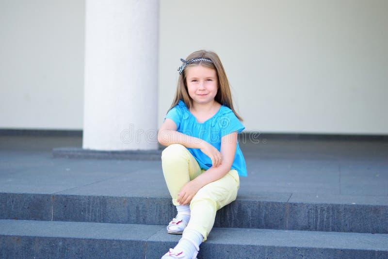 Menina bonita pequena adorável que senta-se em uma escadaria imagens de stock