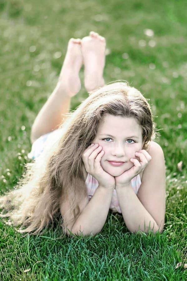 Menina bonita pequena com cabelo fraco longo na grama verde no dia de verão fotos de stock