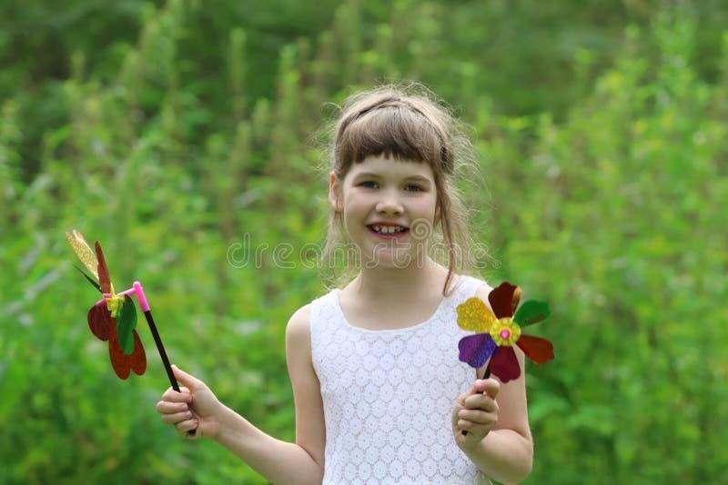 A menina bonita pequena com dois moinhos de vento brinca no verão foto de stock royalty free