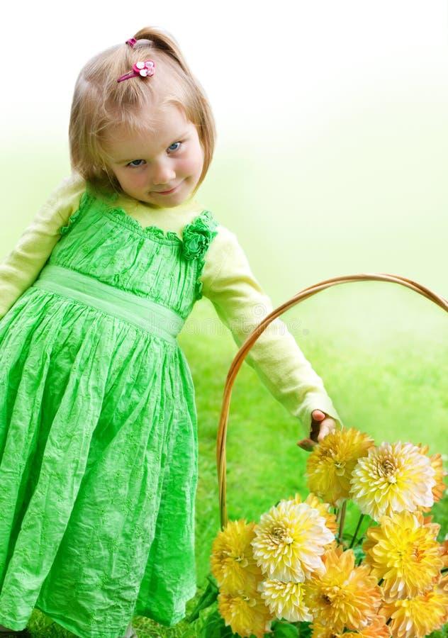 Menina bonita pequena com flores fotos de stock royalty free