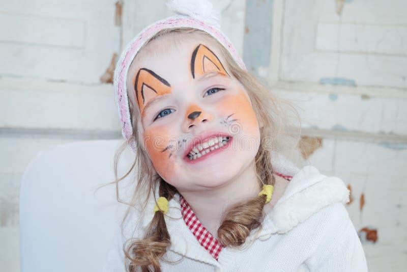 A menina bonita pequena com pintura da cara da raposa sorri fotografia de stock royalty free