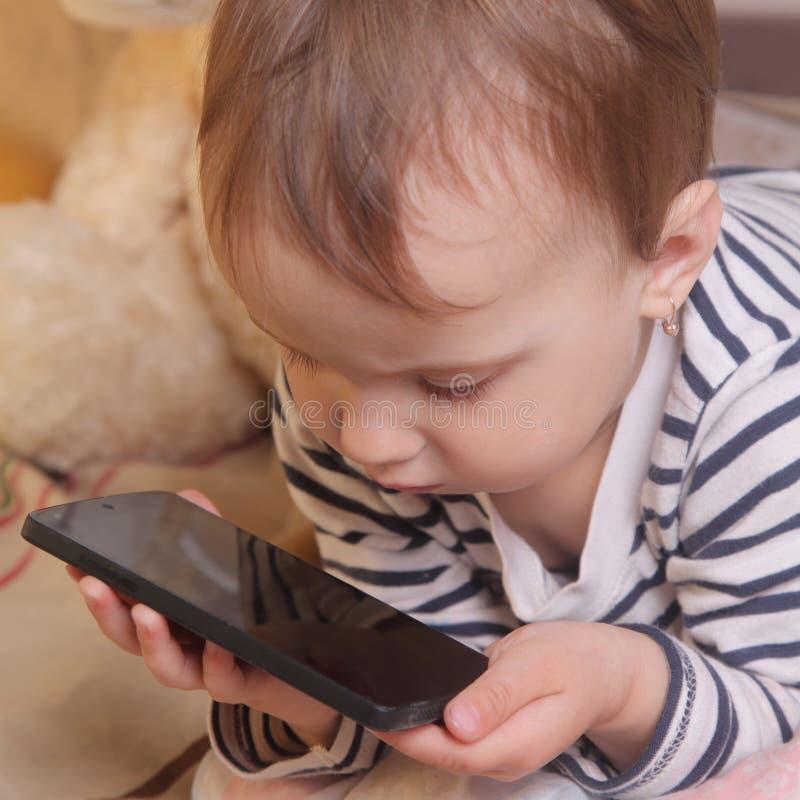 Menina bonita pequena com telefone esperto imagens de stock royalty free