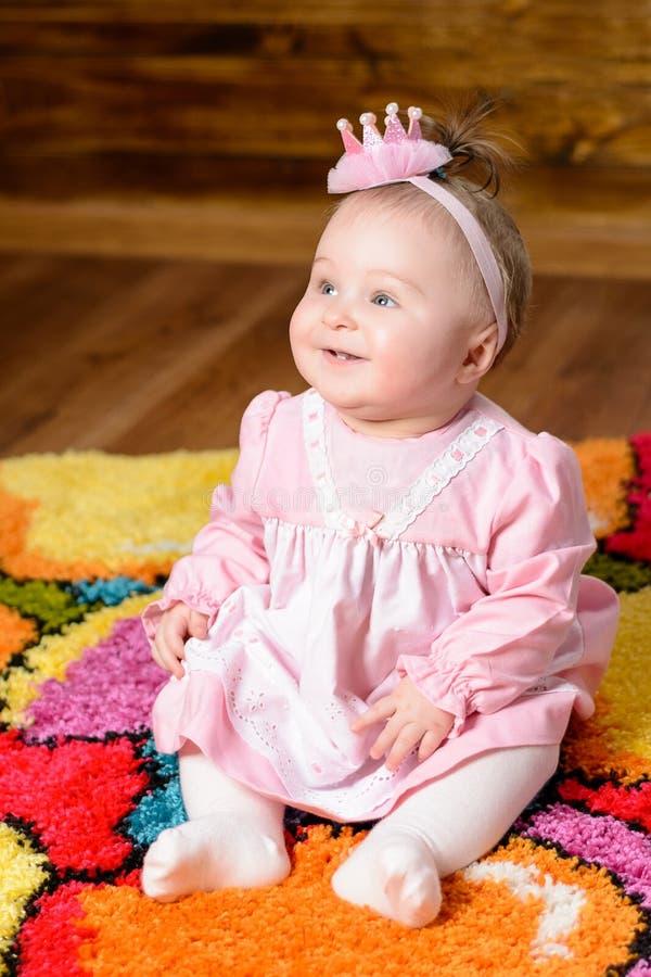 A menina bonita pequena em um vestido cor-de-rosa ri em uma cama de bebê foto de stock