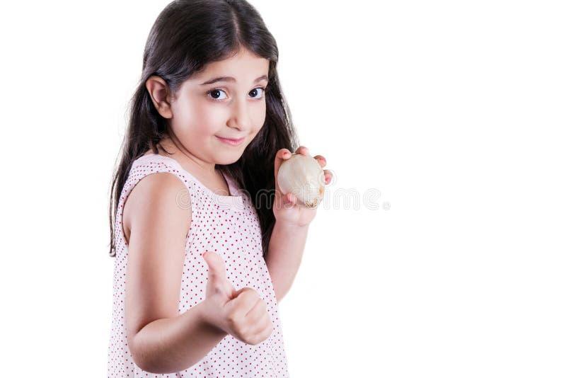 Menina bonita pequena feliz com cabelo escuro e olhos que guardam a cebola branca nas mãos e os polegares que olham acima a câmer fotografia de stock royalty free