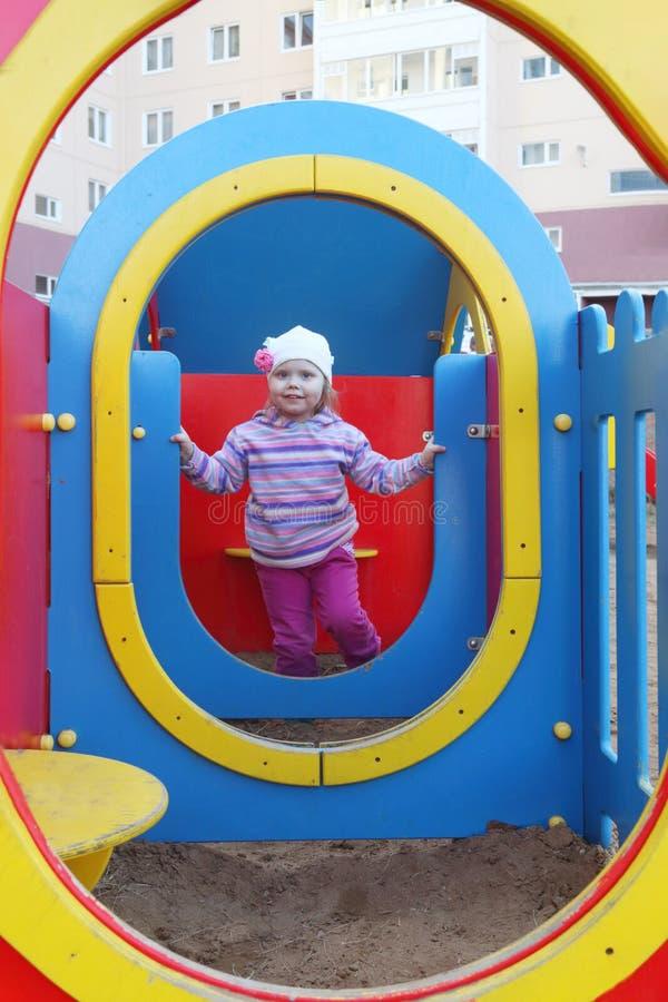 A menina bonita pequena no chapéu joga no campo de jogos das crianças imagens de stock royalty free