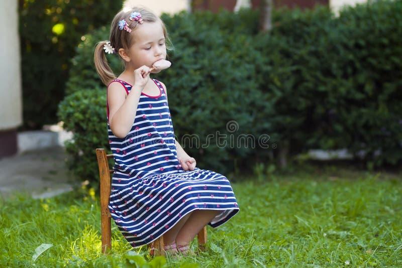 Menina bonita pequena no dia de verão que come um gelado fotografia de stock royalty free