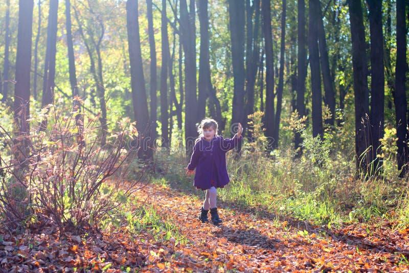 A menina bonita pequena no revestimento corre no parque imagens de stock royalty free