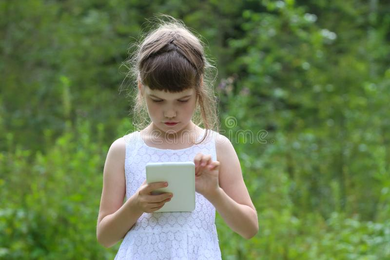 A menina bonita pequena no vestido branco guarda o PC branco da tabuleta fotografia de stock