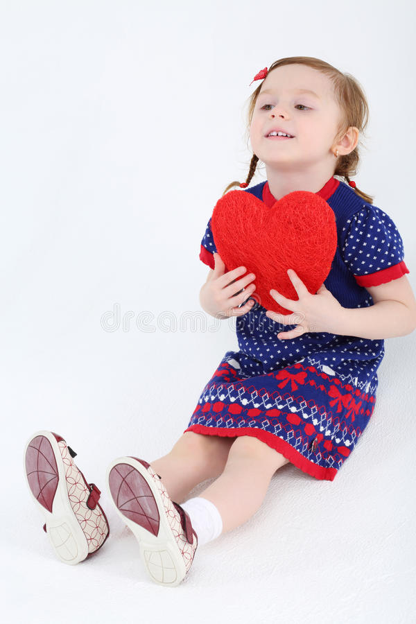 A menina bonita pequena no vestido senta-se no assoalho e guarda-se o coração vermelho imagens de stock royalty free