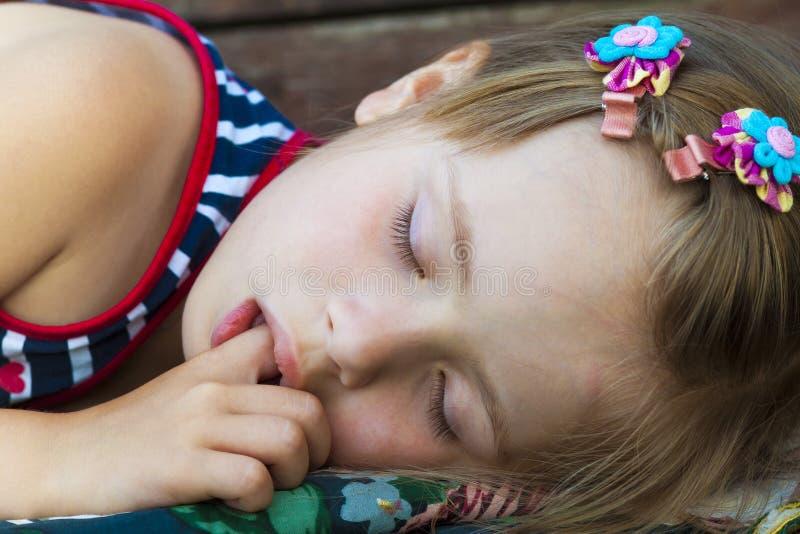 Menina bonita pequena que dorme, sugando o polegar e tendo o drea doce fotografia de stock royalty free