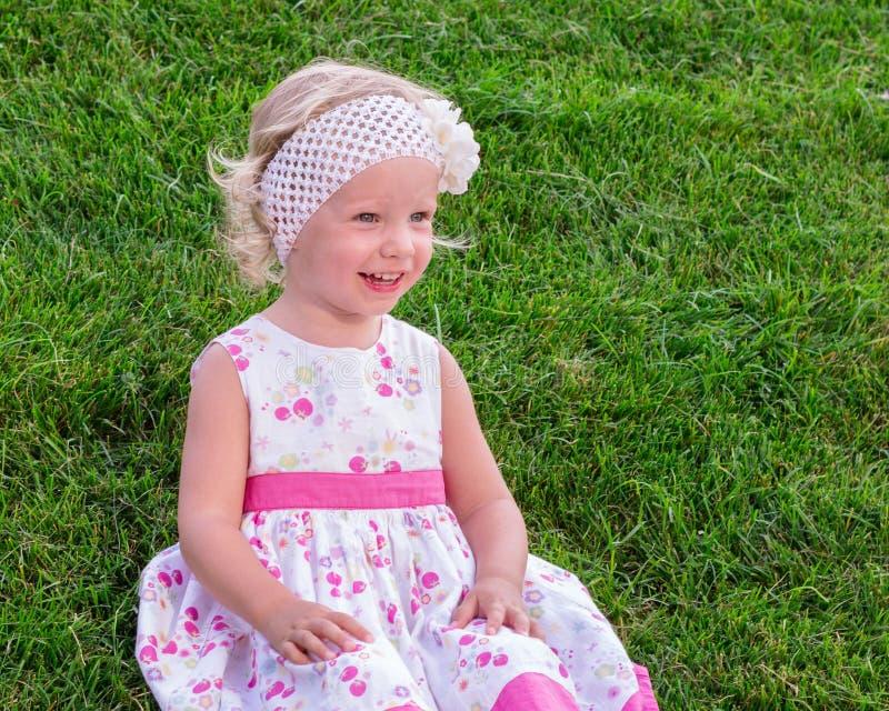 Menina bonita pequena que senta-se na grama verde fotos de stock royalty free